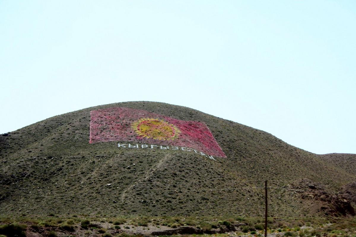 Flaga Kirgistanu usypana z kamieni widoczna z drogi do jeziora